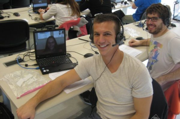 a student in a headset sitting in front of a computer