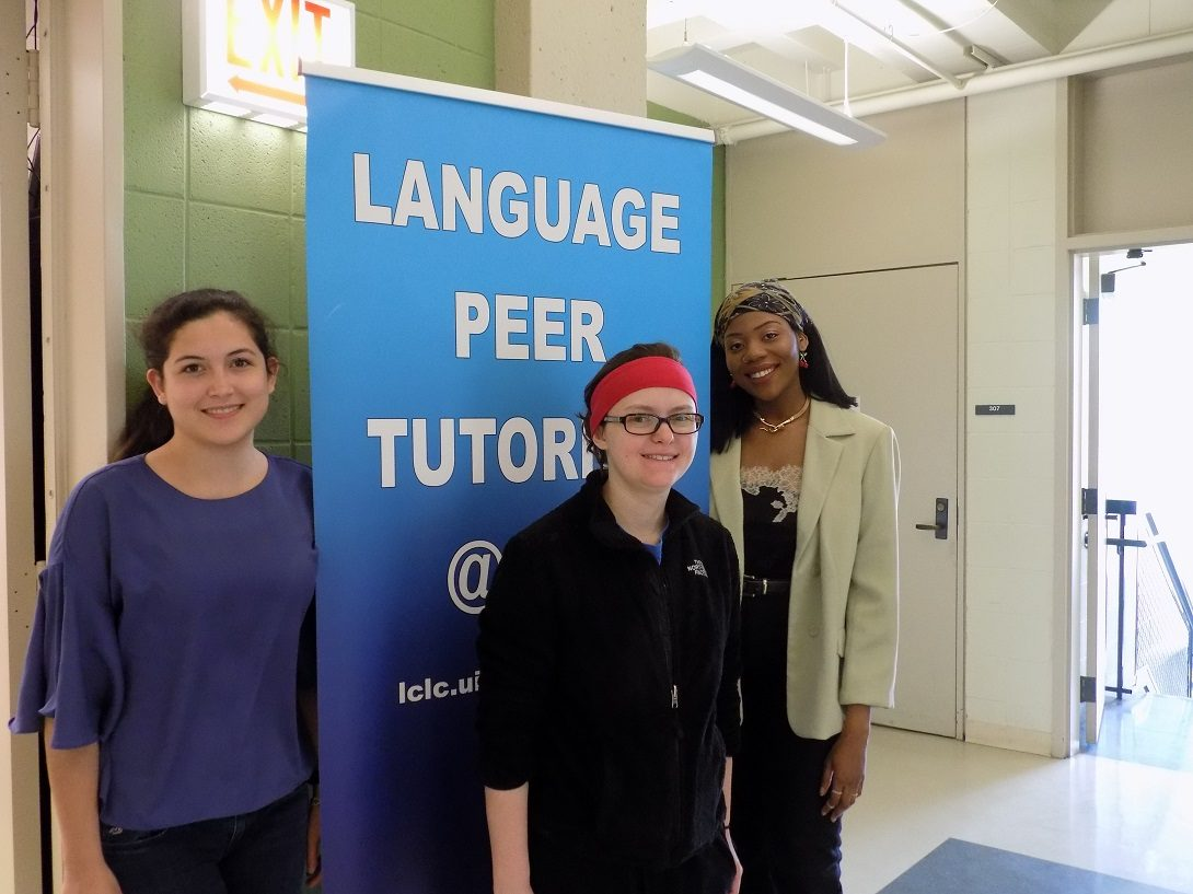 three peer tutors in front of the peer tutoring banner