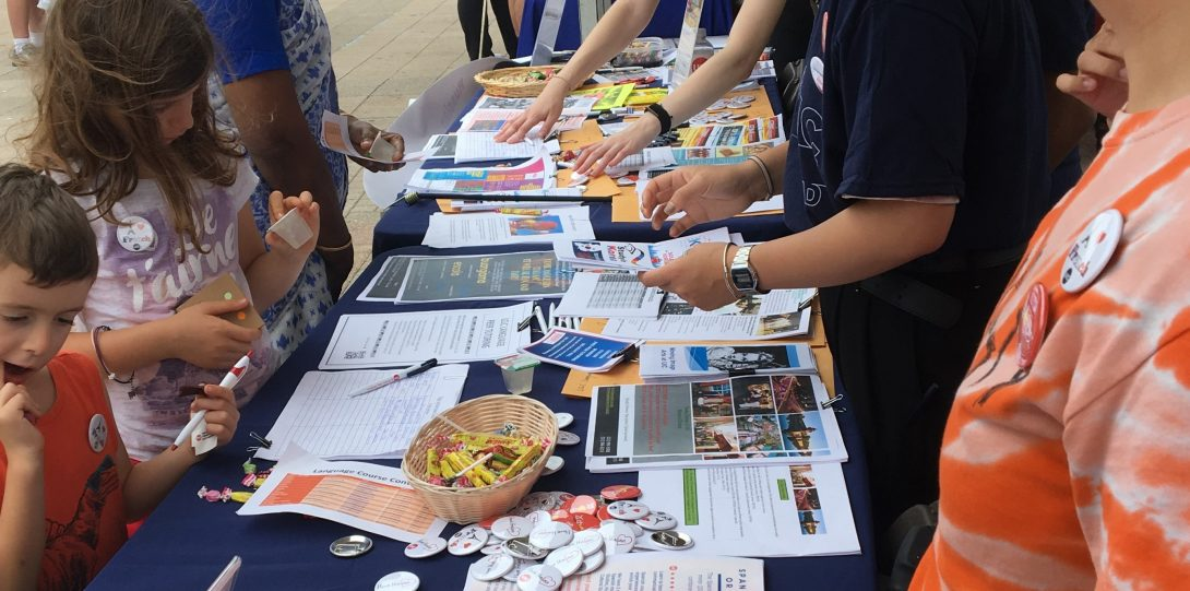 people standing near a table with promotional materials