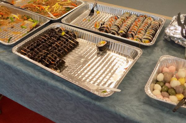 trays of sushi rolls and noodles