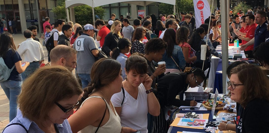 crowd of prospective students near a promotional table