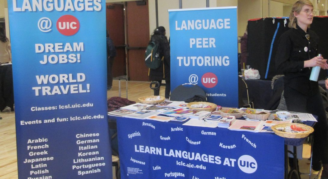 LCLC advertising languages at a fair or open house two banners and a table with many flyers