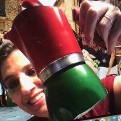 Maria Iusco, Italian lecturer holding an Italian espresso maker and smiling behind it. She is in some public space outside and there are many people behind her.