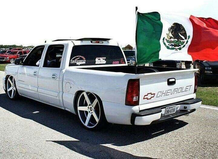 White Chevy truck with flag of Mexico in the truck bed